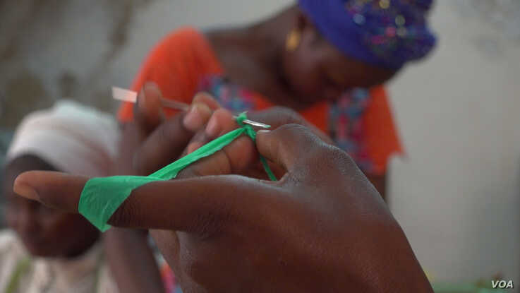 Iness shows how to begin crocheting a basket using strips of plastic (E. Sarai/VOA)