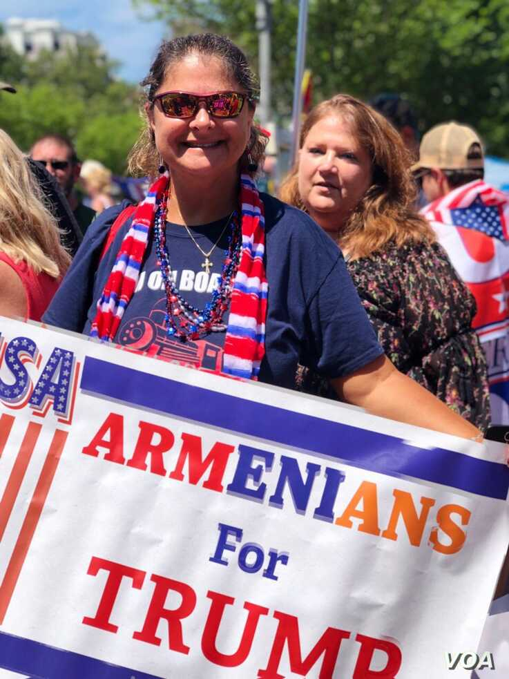 """Caroline Sarajian shows off her """"Armenians for Trump"""" banner, July 4, 2019, on the National Mall in Washington."""