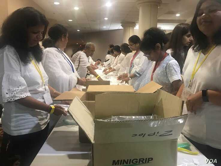 Volunteers of all ages pack hygiene kits for local homeless at long, narrow assembly lines. (Photo: Leslie Bonilla/VOA)