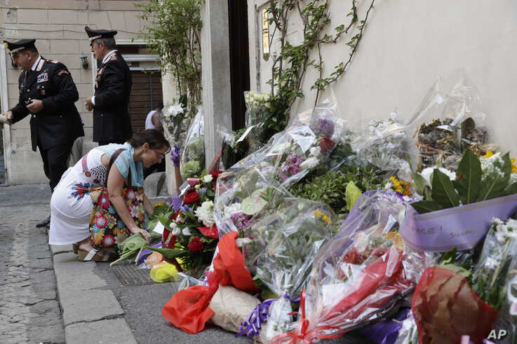 A woman leaves flowers in front of the Carabinieri station where Mario Cerciello Rega was based, in Rome, Saturday, July 27, 2019.