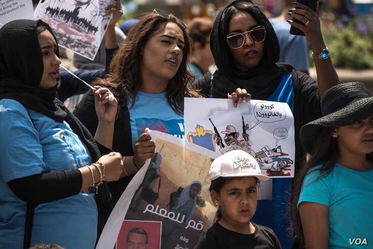 Protesters hold signs and sing at a rally in support of the Sudan's revolution, in Chicago, Illinois, June 29, 2019. (J. Patinkin/VOA)