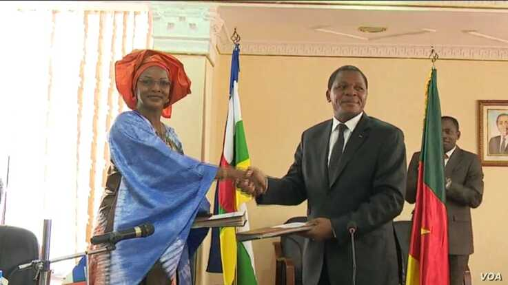 Cameroon minister for territorial administration Paul Atanga Nji, left, and CAR minister for humanitarian action and reconciliation  Viviane Baikou shake hands during a meeting in Yaounde, Cameroon, July 4, 2019. (M. Kindzeka/VOA)