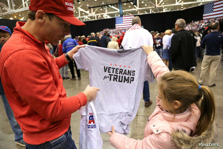 """A supporter of U.S. President Donald Trump looks at a """"Veterans for Trump"""" T-shirt with a young girl at the president's rally in support of Republican candidates on the eve of U.S. midterm elections, in Cleveland, Ohio, Nov. 5, 2018."""