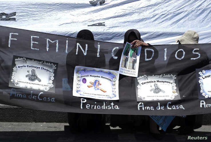 """FILE - Women hold a banner reading """"femicide"""" and with pictures of their relatives during a rally to condemn violence against women in La Paz, Bolivia, Nov. 25, 2014."""