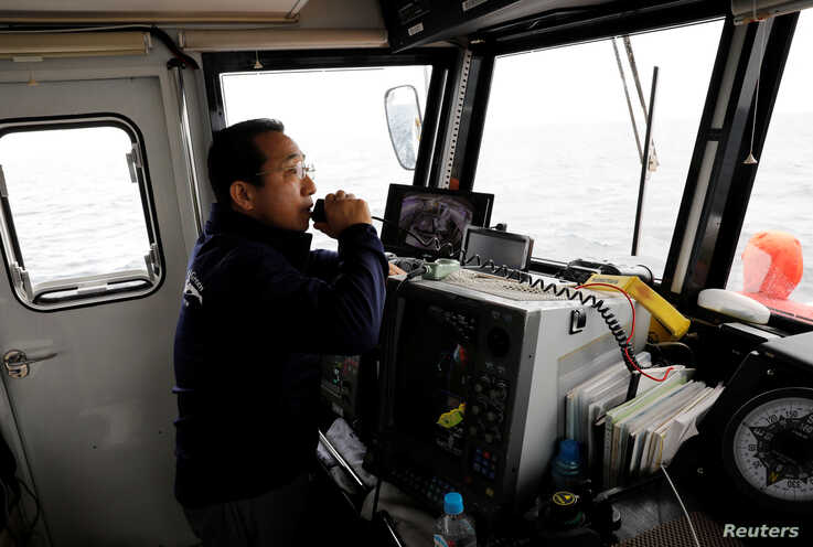 Whale-watching boat captain Masato Hasegawa speaks with other boats in order to look for whales in the sea near Rausu, Hokkaido, Japan, July 1, 2019.
