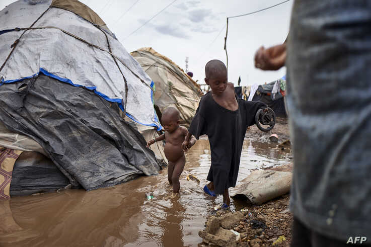 FILE - Two Fulani children walk across a puddle in an Internally Displaced People's (IDP) camp in Faladie, Mali, May 16, 2019.