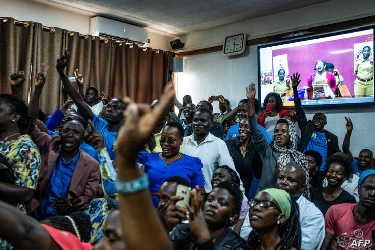 Supporters of jailed activist Stella Nyanzi gesture during her court proceedings near a screen showing her via video link, after she was charged guilty of cyber harassment against Uganda's president, in Kampala courtroom, Aug. 2, 2019.