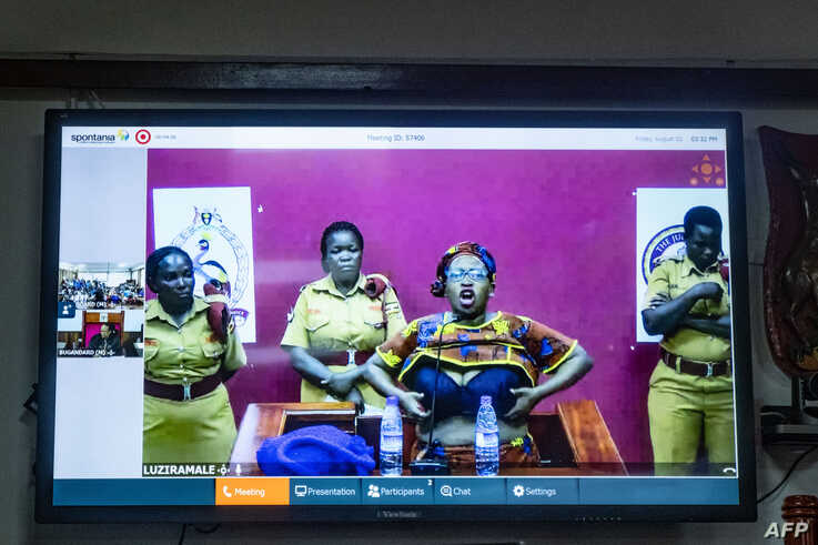 Jailed activist Stella Nyanzi appears by video link as she protests following her sentencing after being charged guilty of cyber harassment against Uganda's president, in Kampala, Aug. 2, 2019.