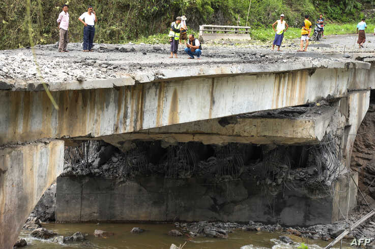 People look at a bomb-damaged bridge outside the compound of the Gote Twin police station in Shan State, Aug. 15, 2019.