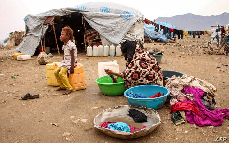 FILE - A woman washes clothes at a make-shift camp for displaced Yemenis who fled fighting between the Houthi rebels and the Saudi-backed government, in the Abs district of the northwestern Hajjah province, Aug. 17, 2019.