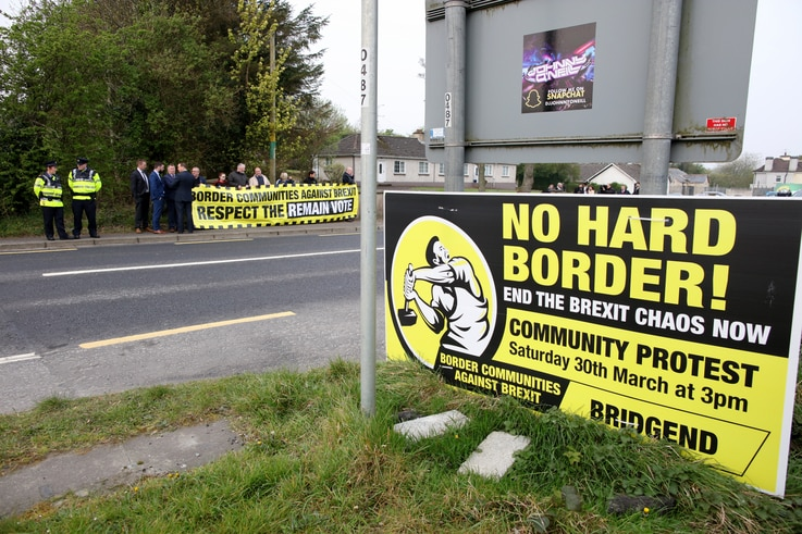 FILE - Protesters against Brexit and the possible imposition of any hard border between Northern Ireland and Ireland gather with a banner near the Irish village of Bridge End, April 18, 2019.