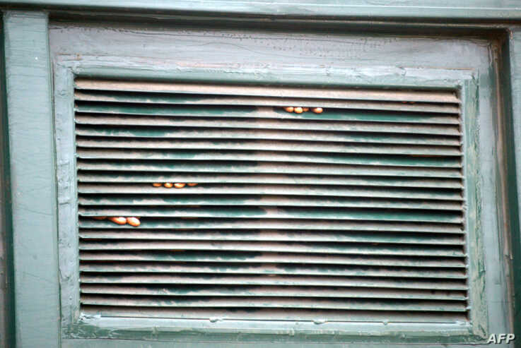 FILE - Arrested prisoners' fingers are seen through a window in September 2005 after a riot by inmates who tried to set fire to part of overcrowed Ikoyi Prison in Lagos, Nigeria.