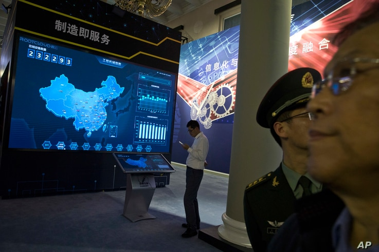 In this Oct. 17, 2017 photo, visitors look at a display of information technologies at an exhibition highlighting China's achievements under five years of Xi's leadership at the Beijing Exhibition Hall in Beijing.
