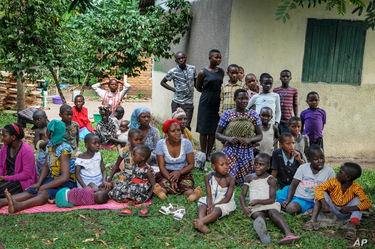 Relatives of the 5-year-old boy who became Ebola's first cross-border victim, and others, listen as village leaders and health workers educate them about Ebola, in the village of Kirembo, June 15, 2019.