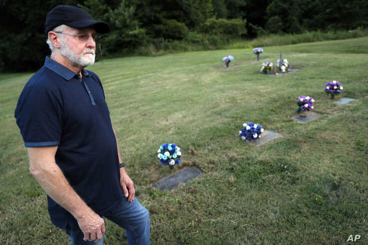 Eddie Davis stands beside the gravestone of his son Jeremy, furthest left, who died from the abuse of opioids at the age of 35, July 17, 2019, in Coalton, Ohio.