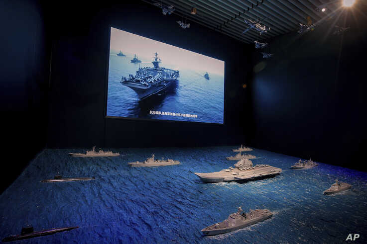 A TV screen showing the U.S. Navy fleet sail in formation near the models of Liaoning aircraft carrier with navy frigates and submarines on display at the military museum in Beijing, Aug. 1, 2019.