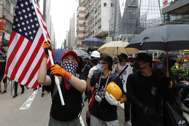 A protester carries a U.S. flag as they march through the Mong Kok neighborhood during a demonstration in Hong Kong, Saturday, Aug. 3, 2019.