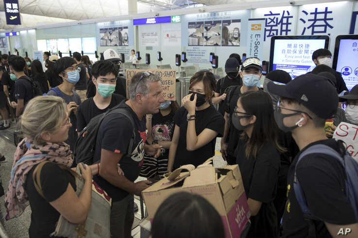 Travelers argue with protesters as they try to go through the departure gates of the Hong Kong International Airport in Hong Kong, Aug. 13, 2019.