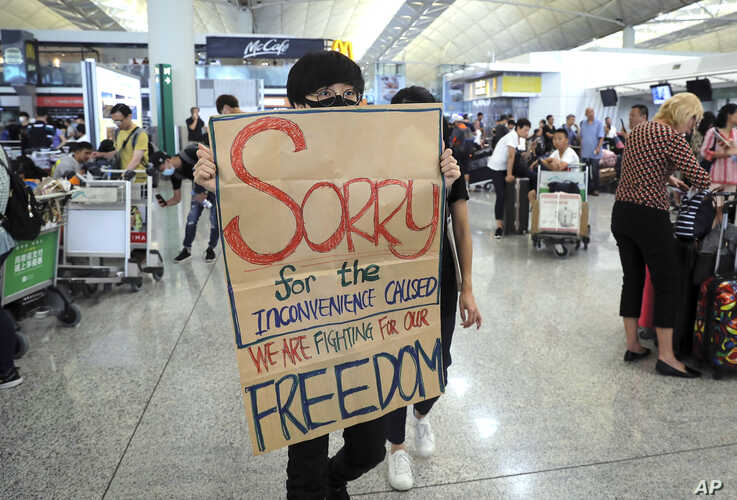 A protester shows a placard to stranded travelers during a demonstration at the Airport in Hong Kong, Aug. 13, 2019.