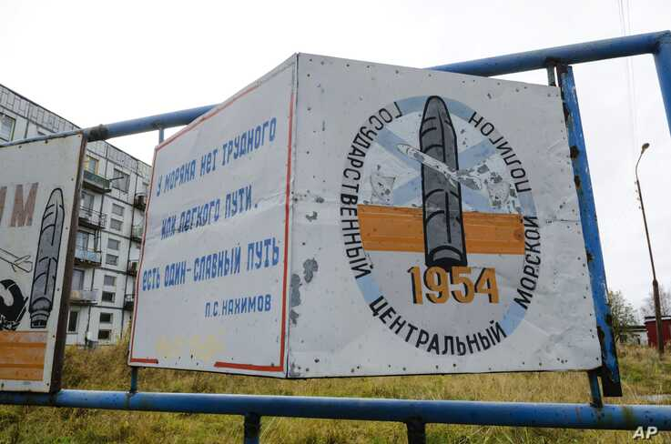 """FILE - A billboard, reading """"The State Central Navy Testing Range,"""" stands near Nyonoksa, Russia, Oct. 7, 2018. An Aug. 8, 2019, explosion of a rocket engine at the Russian navy's testing range just outside Nyonoksa led to a spike in radiation levels."""