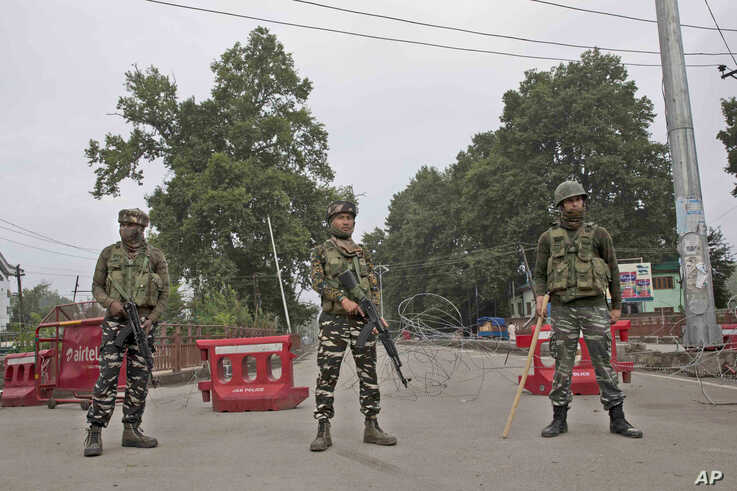 Indian paramilitary soldiers stand guard near a temporary check post on the road leading towards Independence Day parade venue during lockdown in Srinagar, Indian controlled Kashmir, Aug. 15, 2019.