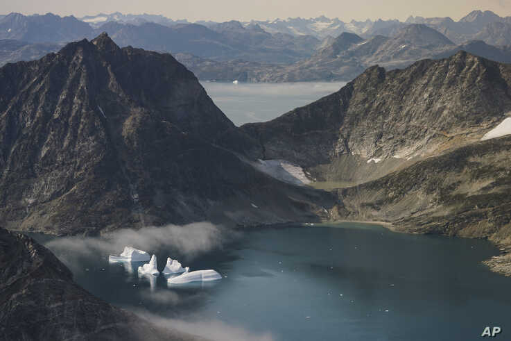 In this photo taken on Wednesday, Aug. 14, 2019, icebergs are photographed from the window of an airplane carrying NASA Scientists as they fly on a mission to track melting ice in eastern Greenland.