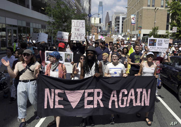 FILE - Protesters assembled by a majority Jewish group called Never Again Is Now walk through traffic as they make their way to Independence Mall in Philadelphia, July 4, 2019.