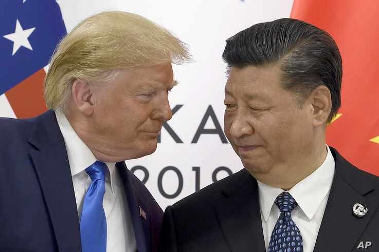 FILE - President Donald Trump, left, meets with Chinese President Xi Jinping on the sidelines of the G-20 summit in Osaka, Japan, June 29, 2019. China will raise tariffs on $75 billion of U.S. products in retaliation for Trump's Sept. 1 duty increase.