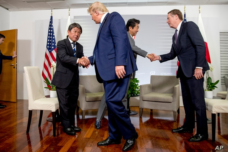 U.S President Donald Trump shakes hands with Japanese Economy Minister Toshimitsu Motegi, left, and Japanese Prime Minister Shinzo Abe, second from right, shake hands with U.S. Trade Representative Robert Lighthizer, following a news conference at the G-7 summit in Biarritz, France, Aug. 25, 2019, where they announced that the U.S. and Japan have agreed in principle on a new trade agreement.