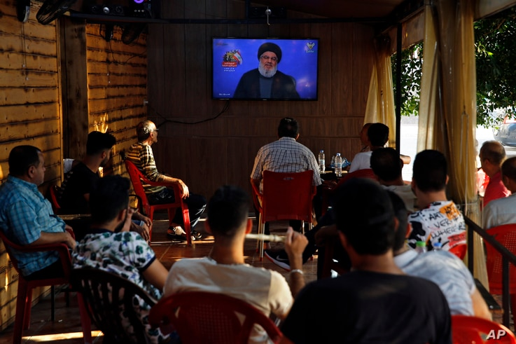 People listen to a speech by Hezbollah leader Sayyed Hassan Nasrallah being broadcast on Hezbollah's al-Manar TV channel, at a coffee shop in a southern suburb of Beirut, Lebanon, Aug. 25, 2019.