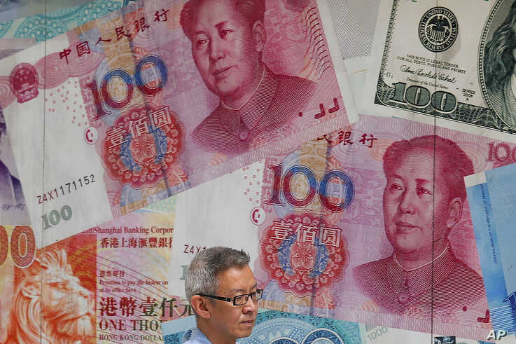 a man walks by a money exchange shop decorated with Chinese yuan banknotes and other countries currency banknotes at Central, a business district in Hong Kong. China allowed its yuan to sink to an 11-year low against the dollar after U.S. President Donald Trump threatened to block American companies from doing business with this country.