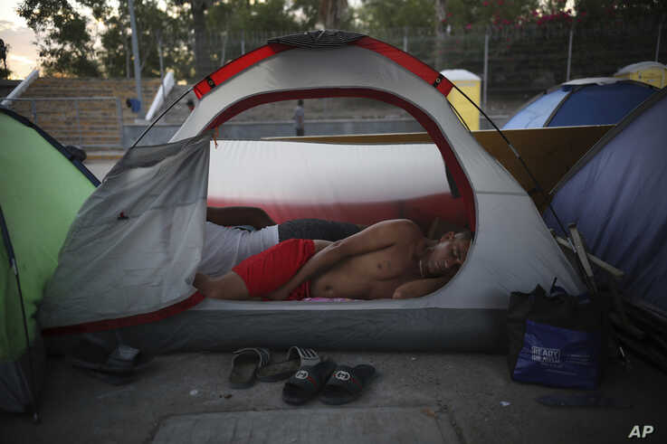 A Cuban migrant sleeps inside a tent at the foot of the Puerta Mexico bridge in Matamoros, Mexico, that crosses the border to Brownsville, Texas, Aug. 4, 2019.