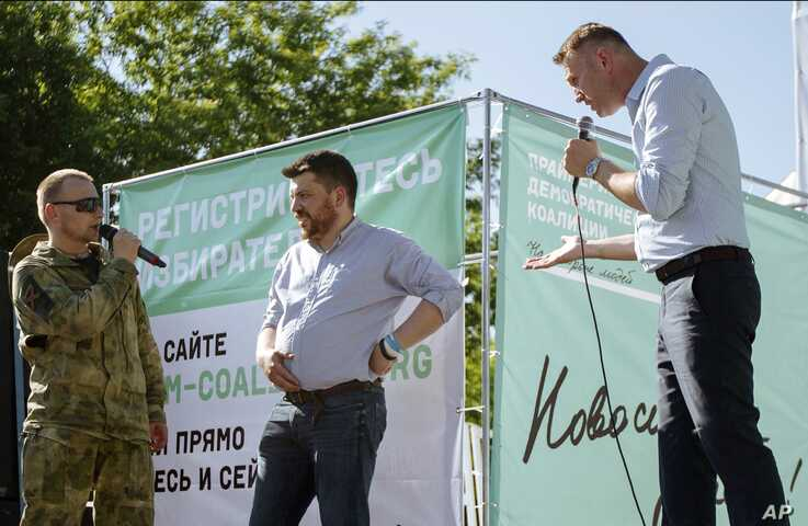 FILE - Russian opposition activist Alexei Navalny, right, argues with a man in a military uniform, left, as opposition activist Leonid Volkov, center, listens during a rally in Novosibirsk, Siberia's biggest city, Russia, June 7, 2015.