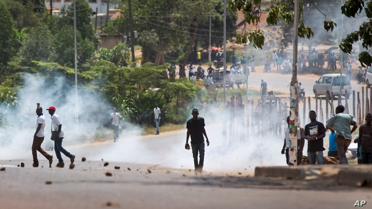 FILE - A voter holds a rock as riot police fire tear gas at a crowd of angry voters outside a polling station where voting material for the presidential election never arrived, at a polling station in Ggaba, Uganda, Feb. 18, 2016.