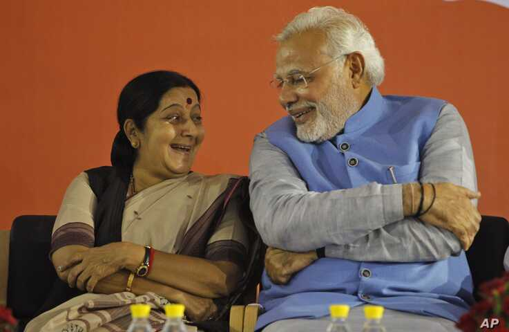 FILE - Opposition Bharatiya Janata Party leader and India's next prime minister Narendra Modi, right, has a laugh with party leader Sushma Swaraj during a press conference at the party headquarters in New Delhi, India, May 17, 2014.