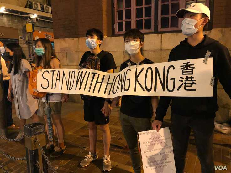 "Hong Kong protesters gather outside the subway station in Sheung Wan district participate the ""823 Road for Hong Kong"" human cha"