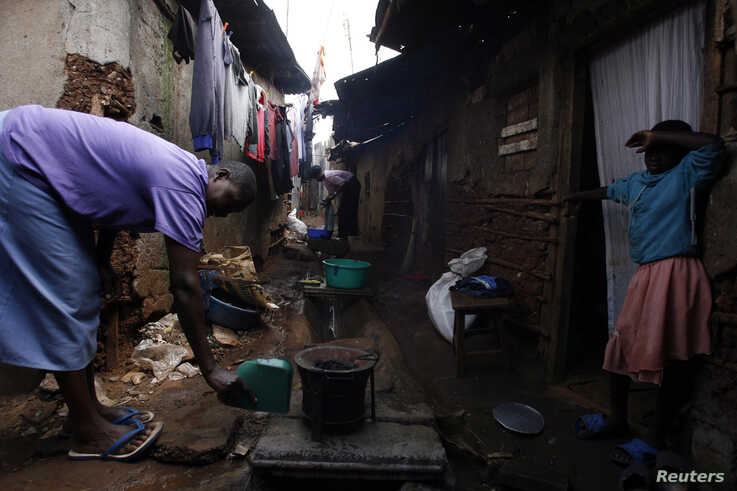 FILE - A woman lights a charcoal stove in an alley in Nairobi's Kibera slum, Feb. 6, 2008.