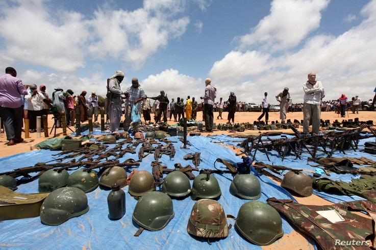 FILE - Al-Shabab Islamist militants display weapons believed to be recovered peacekeepers suspected to have been killed during fighting in Somalia's capital Mogadishu, Oct. 21, 2011.