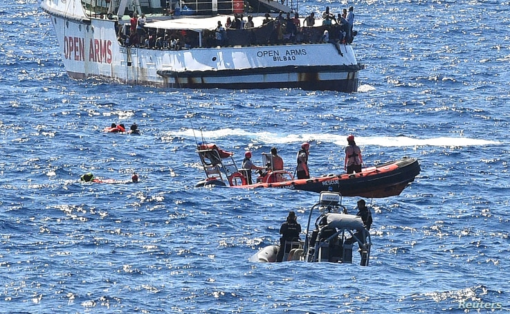 Migrants swim after jumping off the Spanish rescue ship Open Arms, close to the Italian shore in Lampedusa, Italy, Aug. 20, 2019.