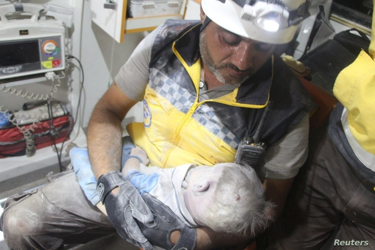A Syria Civil Defence (White Helmets) member holds a child victim, pulled from the rubble after a deadly airstrike, said to be in Maarat al-Numan, Idlib province, Syria, Aug. 28, 2019.