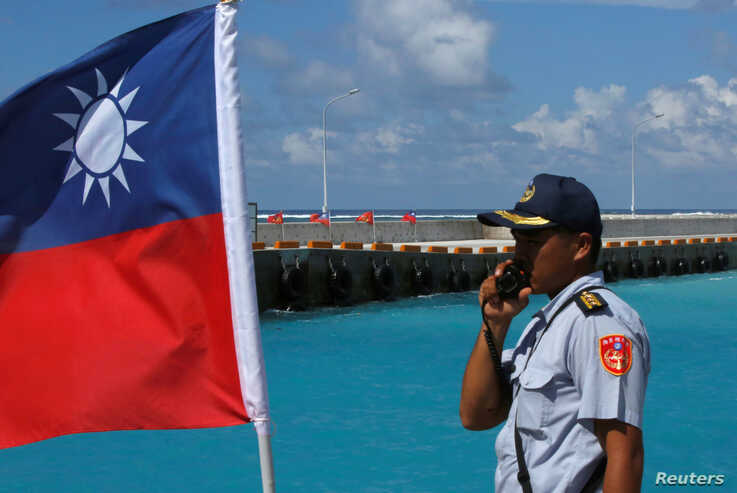 FILE - A member of the Taiwanese Coast Guard stands guard next to a Taiwanese flag on Itu Aba, which the Taiwanese call Taiping, at the South China Sea, Nov. 29, 2016.