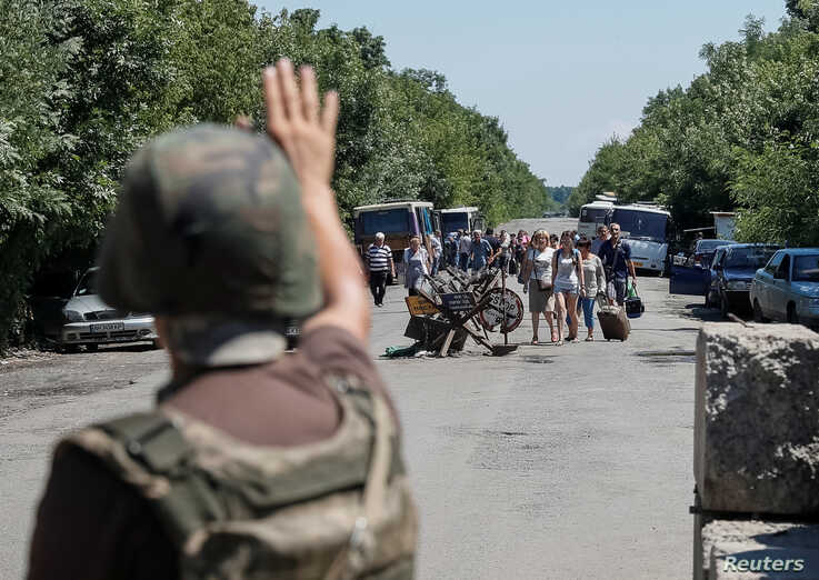 A member of the Ukrainian State Border Guard Service gives a sign to people to stop as they approach a checkpoint at the contact line between pro-Russian rebels and Ukrainian troops in Mayorsk, Ukraine July 3, 2019.