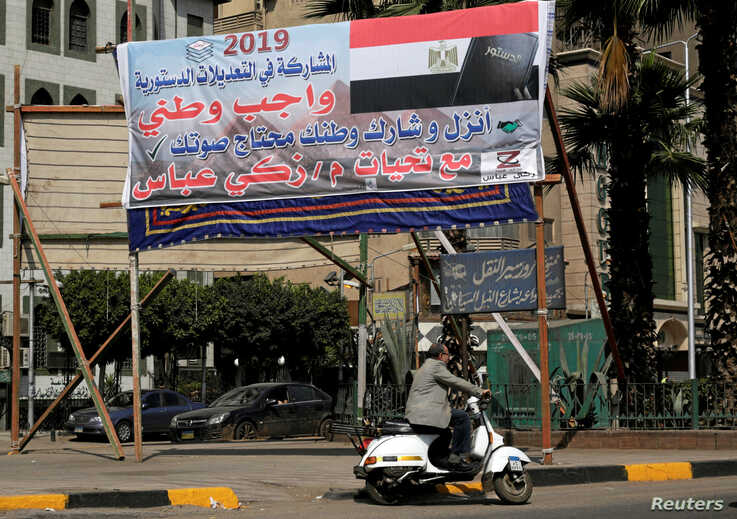 """A man drives his motorcycle in front of a banner reading in Arabic, """"Participation in constitutional amendments is a national duty"""", in Cairo, Egypt April 3, 2019."""