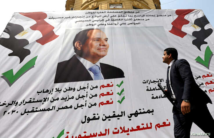 """A man walks in front of a banner reading, """"Yes to the constitutional amendments, for a better future"""", with a photo of the Egyptian President Abdel Fattah al-Sisi before the referendum on constitutional amendments in Cairo, Egypt April 16, 2019."""