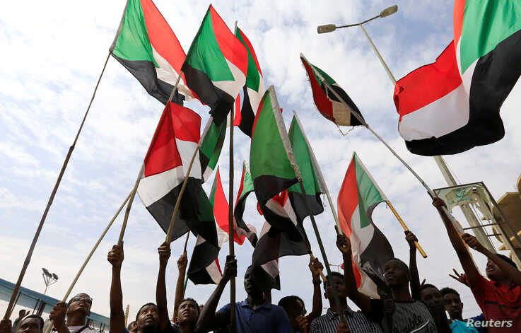 People wave national flags as they demonstrate against the killing of protesting children, who were shot dead when security forces broke up a student protest in Khartoum, Sudan, Aug. 1, 2019.