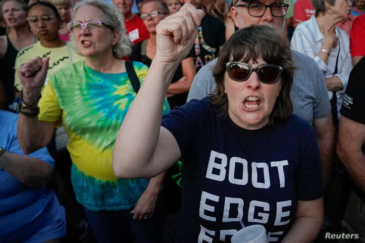 """FILE - People shout """"Do Something!"""" as Ohio Governor Mike DeWine speaks during a vigil at the scene of a mass shooting in Dayton, Ohio, Aug. 4, 2019."""