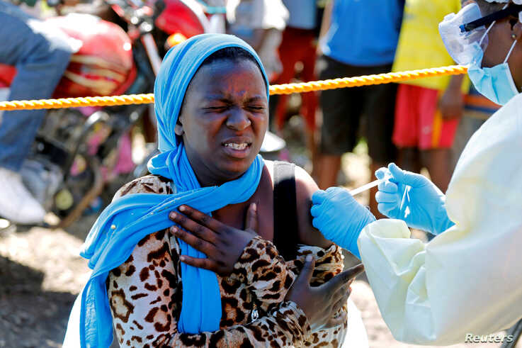 FILE - A woman reacts as a health worker injects her with the Ebola vaccine, in Goma, Democratic Republic of Congo, Aug. 5, 2019.