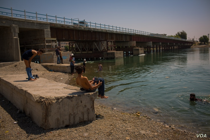 Residents enjoy the cold waters of the Euphrates River during the hot days of summer, Aug. 25, 2019 in Raqqa, Syria. (Yan Boechat/VOA)