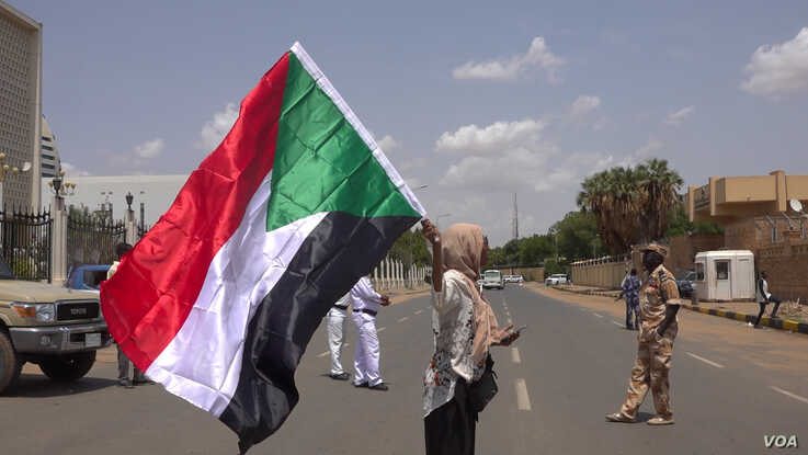 Hiba Salah waves Sudan's flag outside Friendship Hall as the agreement is being signed (E. Sarai/VOA)