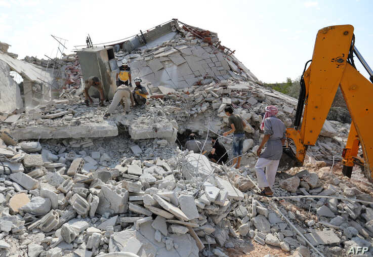 Members of the Syrian Civil Defense (White Helmets) search for victims amidst the rubble of a building that collapsed during reported airstrikes by pro-regime forces in the village of Beinin in the northern Idlib province,  Aug. 20, 2019.